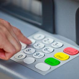 Un individu compose son code confidentiel pour faire un retrait sur un GAB